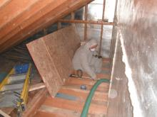 An Orange Energy crew member installs cellulose insulation in the attic space after air sealing.